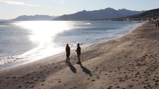 Couple walk along beach, skip rocks out to sea