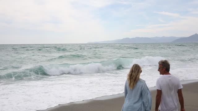 stockvideo's en b-roll-footage met couple walk along beach towards crashing surf - hemden en shirts