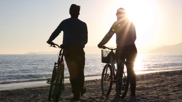 vídeos y material grabado en eventos de stock de couple walk along beach with bikes, sunset - manta ropa de cama