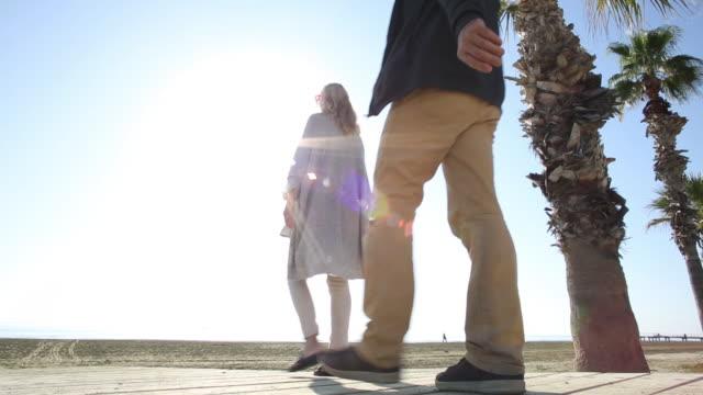 couple walk along boardwalk to empty beach - boardwalk stock videos & royalty-free footage