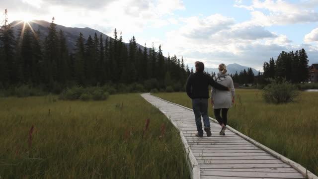 couple walk along boardwalk towards sunrise - 腰に手を当てる点の映像素材/bロール