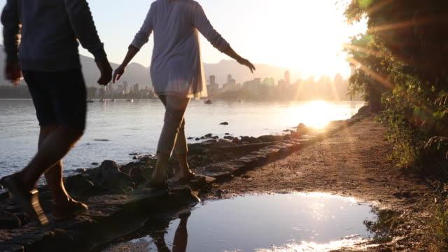 couple walk along coastal pathway, city skyline behind - lens flare stock videos & royalty-free footage