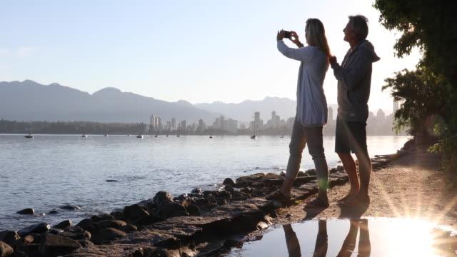 couple walk along coastal pathway, city skyline behind - pedal pushers stock videos & royalty-free footage