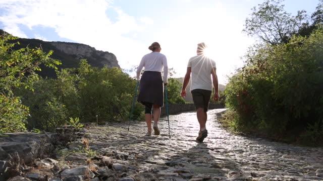 stockvideo's en b-roll-footage met couple walk along cobblestone corridor, on green hillside - kassei