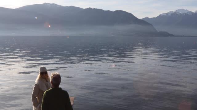 vídeos de stock e filmes b-roll de couple walk along curving pier above mountain lake - casal de meia idade