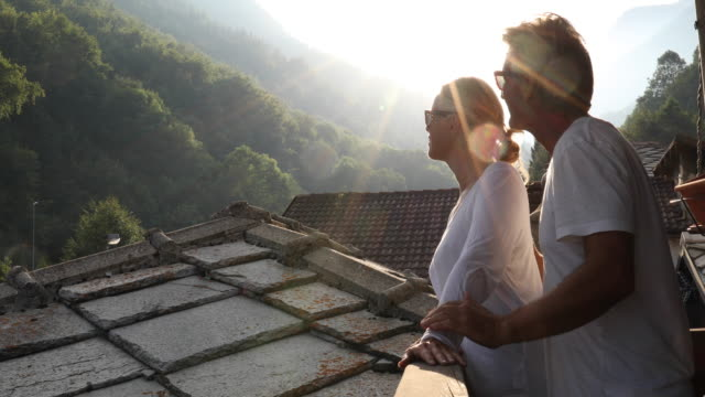 couple walk along deck, look out to mountain landscape - slate rock stock videos and b-roll footage