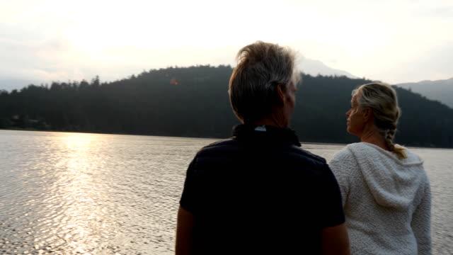 couple walk along dock at sunrise - lake stock videos & royalty-free footage