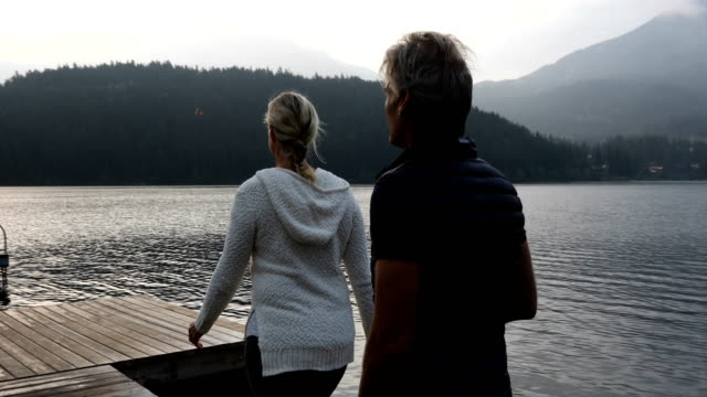 couple walk along dock at sunrise - north america stock videos & royalty-free footage
