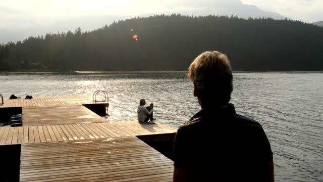 vídeos de stock e filmes b-roll de couple walk along dock at sunrise - casal de meia idade