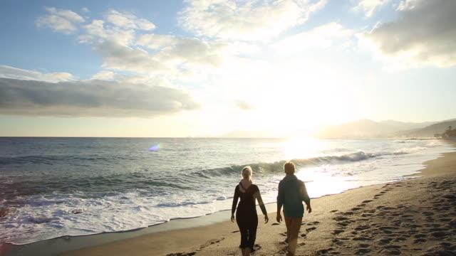 couple walk along empty beach at sunrise, looking out to sea - incontro romantico video stock e b–roll