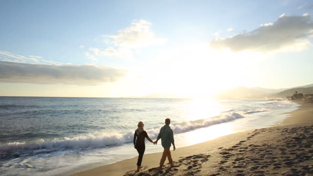 Couple walk along empty beach at sunrise, looking out to sea