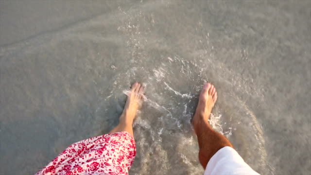 Couple walk along empty beach, view towards feet