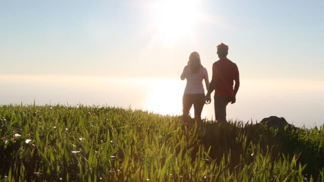 couple walk along grassy ridge crest above sea - achievement点の映像素材/bロール