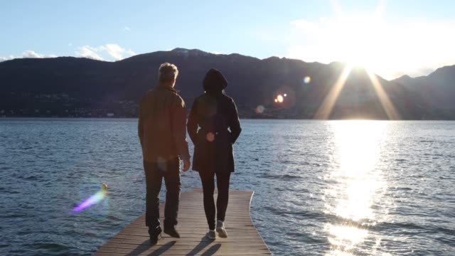 couple walk along lake pier at sunrise - see other clips from this shoot 56 stock videos & royalty-free footage