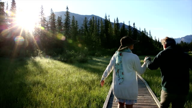 couple walk along mountain boardwalk towards sunrise - hat stock videos and b-roll footage