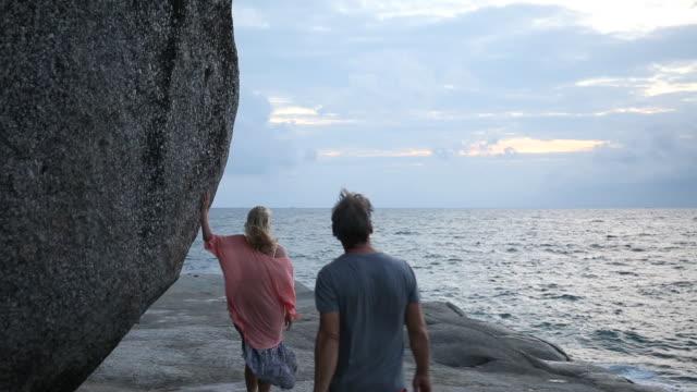 Couple walk along rock slabs above sea, boulders