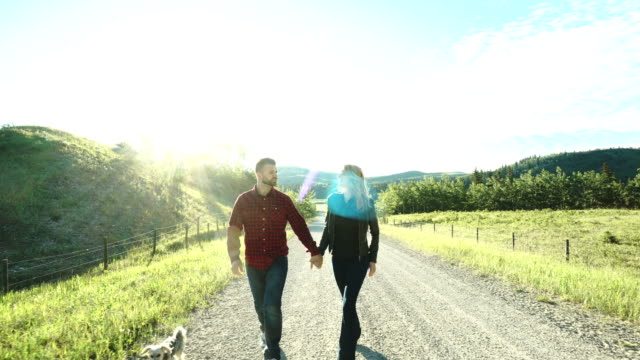 Couple walk along rural path, look out across meadow and forest