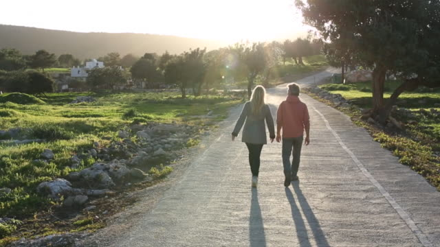 Couple walk along rural road at sunrise