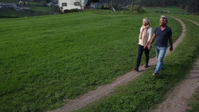 Couple walk along rural track through green field, below village