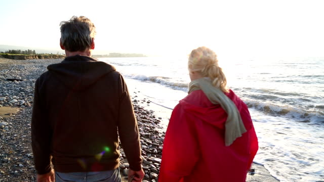 couple walk along sand and pebble beach - adventure stock videos & royalty-free footage