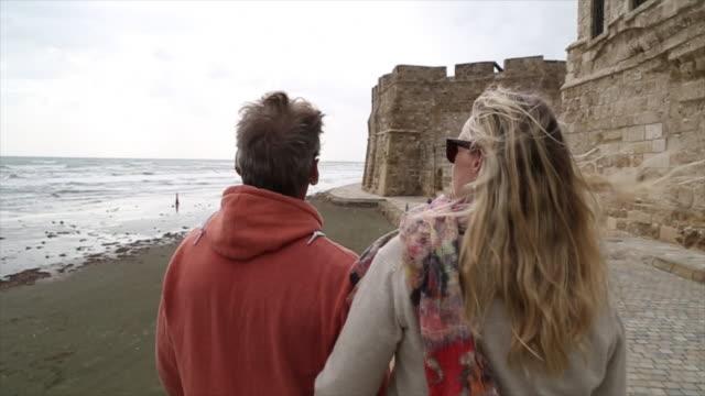 Couple walk along sea promenade, looking off