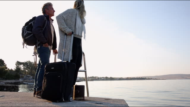 Couple walk along sea promenade, with luggage