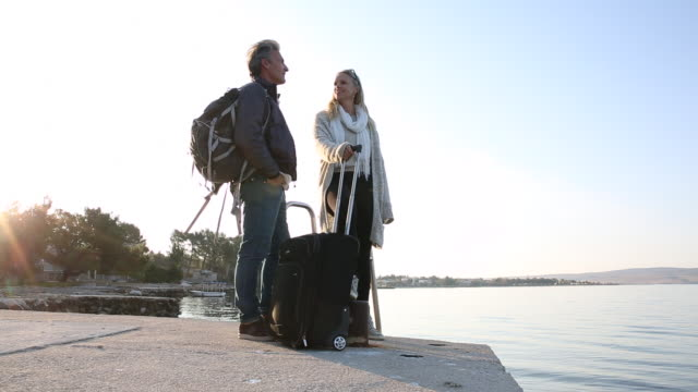 couple walk along sea promenade, with luggage - luggage stock videos & royalty-free footage