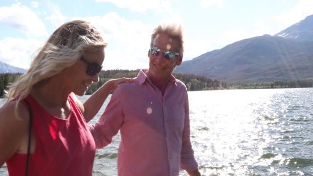 Couple walk along shoreline of mountain lake