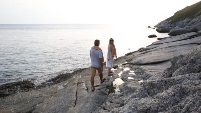 couple walk along shoreline rocks, look out over sea - tide pool stock videos & royalty-free footage