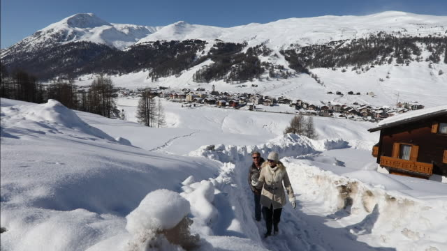 couple walk along snowy corridor in mountain village - tourism stock videos & royalty-free footage