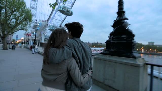 A couple walk along the River Thames near the Millennium Wheel.