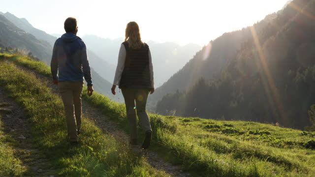 Couple walk along track above mountain ranges, sunrise