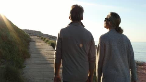 couple walk along wooden boardwalk, talking - arm around stock videos & royalty-free footage