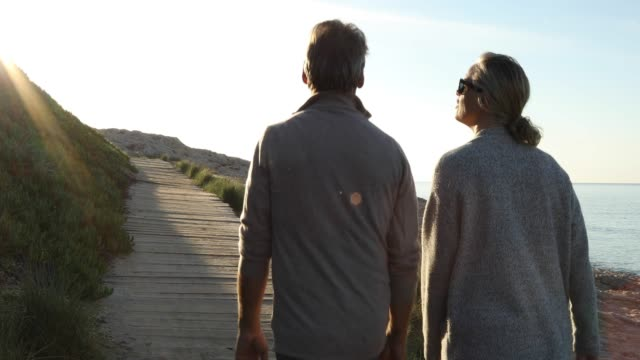 couple walk along wooden boardwalk, talking - arm around stock videos & royalty-free footage