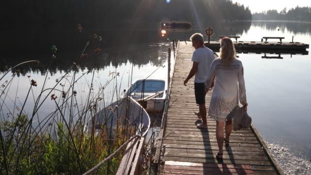 couple walk along wooden lake dock at sunrise - beckoning stock videos & royalty-free footage