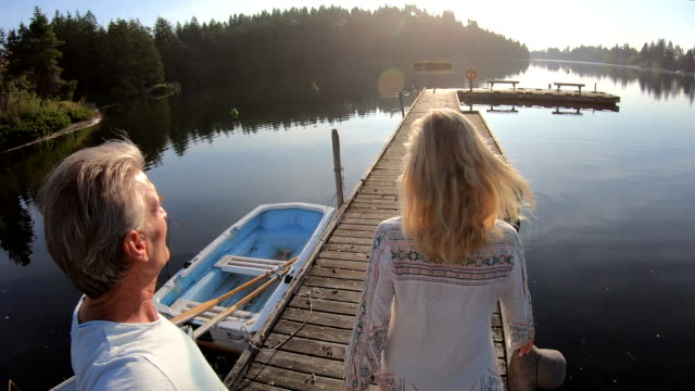 couple walk along wooden lake pier at sunrise - pier stock videos & royalty-free footage