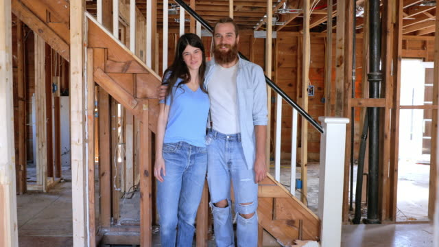 couple walk and stand in front of stairs in renovated home - t shirt stock videos & royalty-free footage