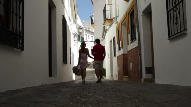 LS couple walk away from camera down cobbled street in quaint town/Genalguacil/Andalucia/Spain
