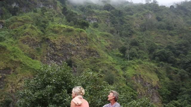 couple walk below rainforest cliff, waterfall, look uo - korta ärmar bildbanksvideor och videomaterial från bakom kulisserna