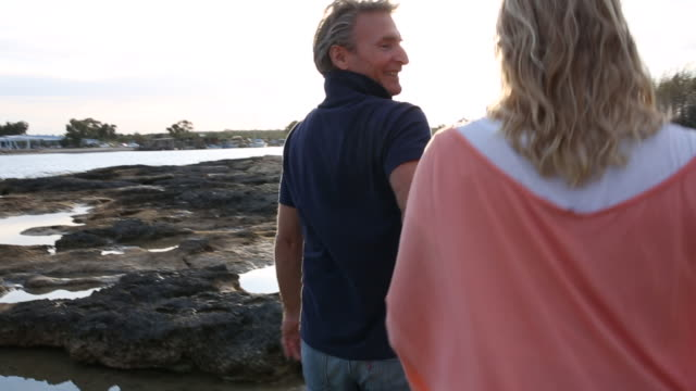 couple walk between tidal pools, over shoreline rocks - tunic stock videos & royalty-free footage