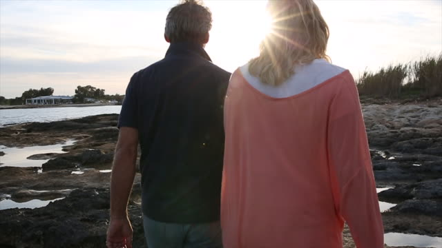 Couple walk between tidal pools, over shoreline rocks