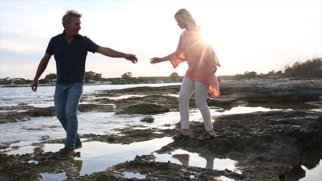 vidéos et rushes de couple walk between tidal pools, over shoreline rocks - se tenir par la main