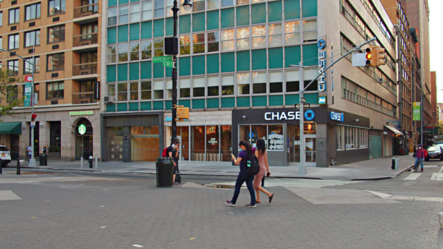 couple walk by chase bank on a new york city street. urban. - bank stock videos & royalty-free footage