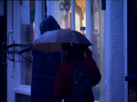 couple walk down street then stop to look in shop window devon - waterproof clothing stock videos and b-roll footage