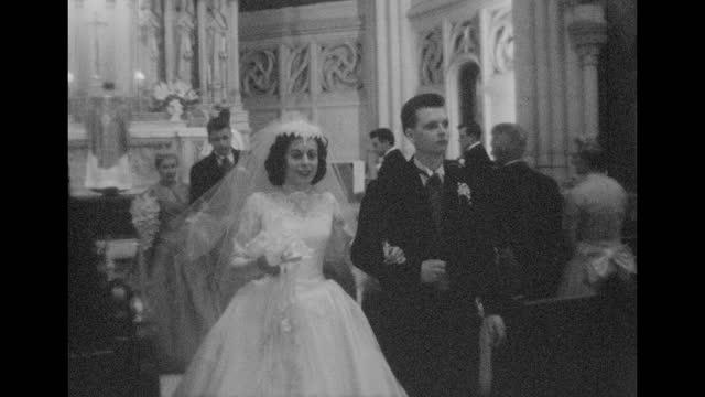 vidéos et rushes de a couple walk down the aisle in a church after they get married. - image en noir et blanc