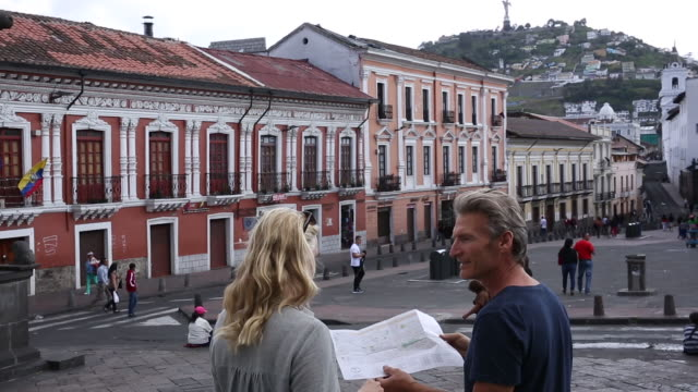 couple walk into city piazza, holding map - ecuador stock videos & royalty-free footage