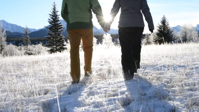 Couple walk into frosty mountain meadow, sunrise