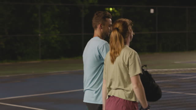 couple walk off tennis court at night, handheld - competition stock videos & royalty-free footage