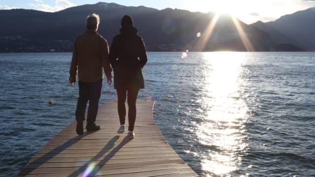 vidéos et rushes de couple walk onto lake pier, they look out to view - 55 59 ans
