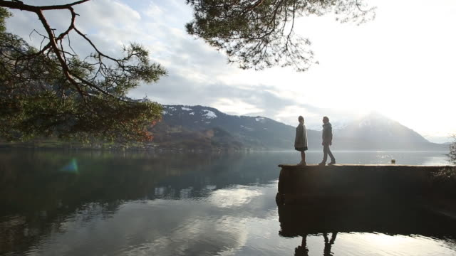 couple walk onto lakeside beach, mountains distant - distant stock videos and b-roll footage